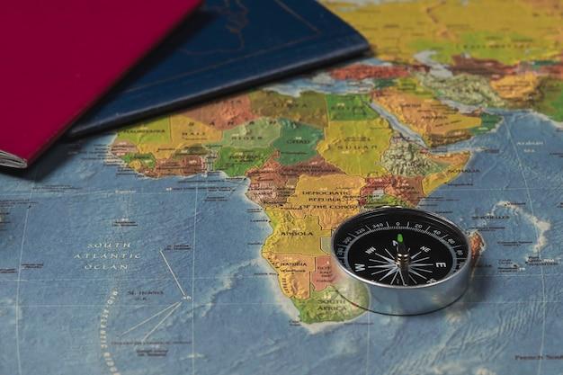 Een kompas op de wereldkaart en paspoorten.