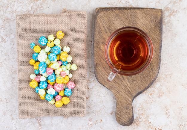 Een kop hete thee met kleurrijke snoepjes