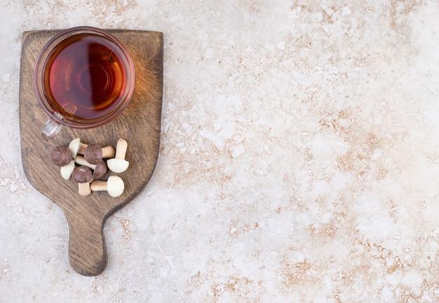 Een kop hete thee met zoete champignons op een houten bord
