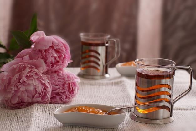 Een kop hete thee naast een schotel met dessert en drie pioenrozen, ontbijt voor twee