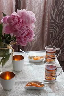 Een kop hete thee naast een schotel met dessert en een boeket pioenrozen, ontbijt voor twee