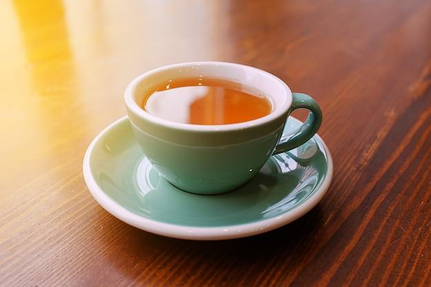 Een kop hete verkwikkende en opwarming van de thee op een houten tafel, ochtendthee. selectieve aandacht. de foto is bedekt met korreligheid en ruis.
