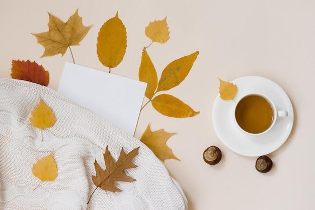 Een kop hete zwarte thee, gevallen herfstbladeren, een vel wit, blanco kopieerpapier en een gebreid wit plaid op beige