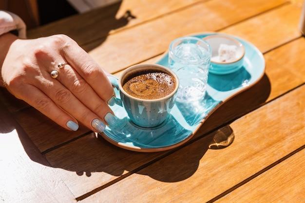 Een kop hete zwarte turkse koffie in blauwe kop in handen van vrouwen geserveerd met een glas water en suiker