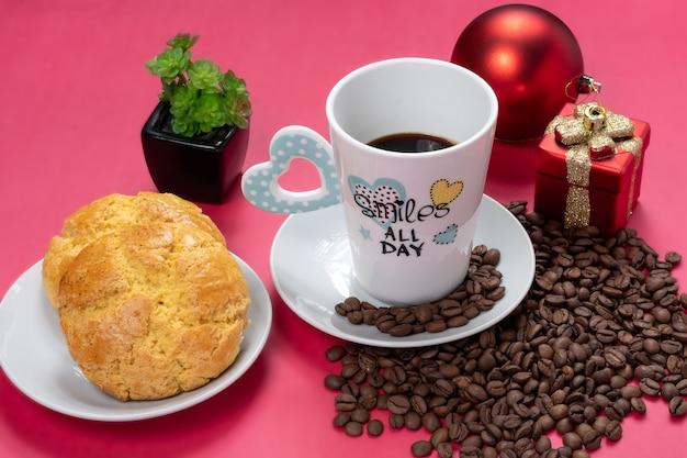 Een kop koffie met melk en koekjes wat koffiebonen met kerstdecoratie op een roze achtergrond