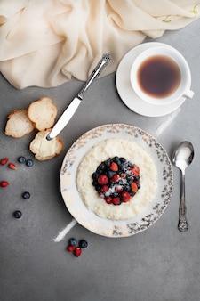 Een kop thee en rijstebrij met bessen op een grijze steenachtergrond.