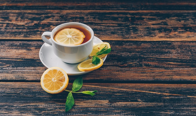 Een kop thee met mening van de citroen de hoge hoek over een donkere houten ruimte als achtergrond voor tekst