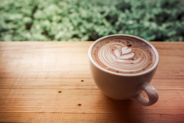 Een kop van koffie latte kunst met hart in een witte kop met groen verlofkader