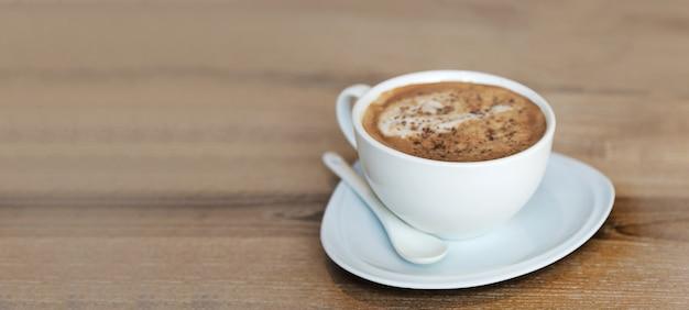 Een kop warme cappucinno serveren op houten tafel in bannerformaat