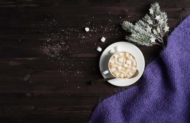 Een kop warme chocolademelk, een gebreide deken en sparren takken op een donkere houten achtergrond met sneeuw.