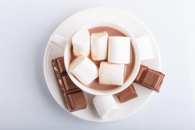 Een kop warme chocolademelk met marshmallow en melkchocola op wit wordt geïsoleerd.