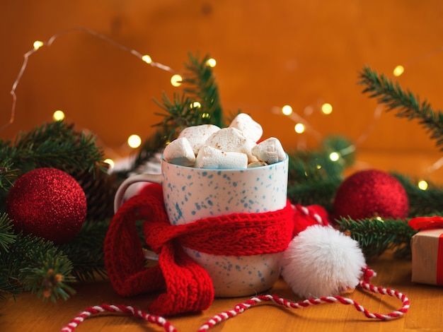 Een kop warme koffie, cacao of chocolade met marshmallows, een zoet dessert. rode sjaal op een mok, vakantiedecor