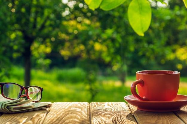 Een kop warme koffie en glazen met een krant op een houten tafel in een groene tuin in de ochtend