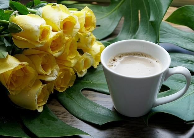 Een kop warme koffie met een prachtig geel rozenboeket