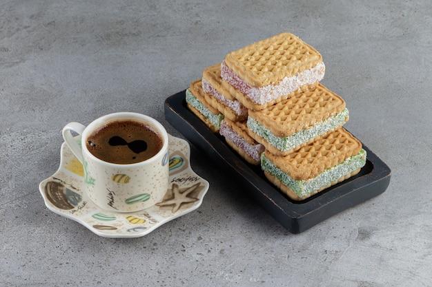 Een kop warme koffie met een zwart bord met zoete wafels op een steen