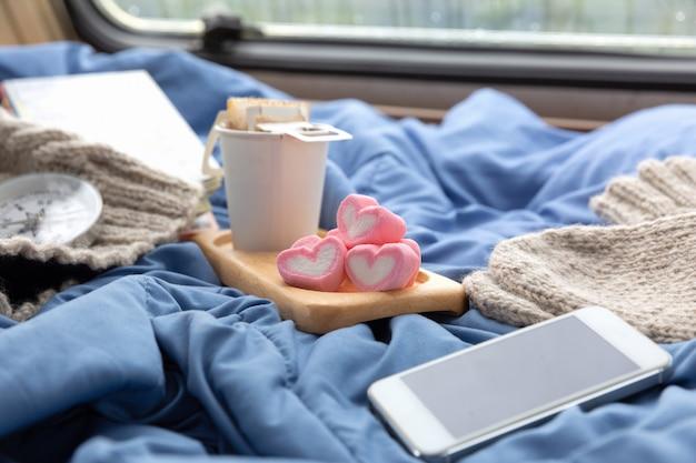 Een kop warme koffie met marshmallow bij het raam in de caravan