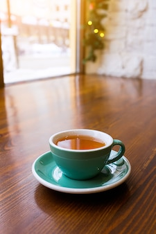Een kop warme verkwikkende en opwarming van de thee op een houten tafel, ochtendthee op eerste kerstdag. selectieve aandacht. de foto is bedekt met gruis en ruis.