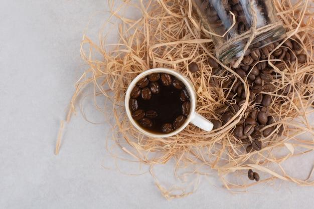 Een kopje aromakoffie met een pot vol bonen op hooi. hoge kwaliteit foto