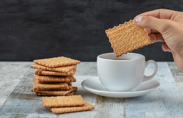 Een kopje aromathee met crackers op een houten tafel.
