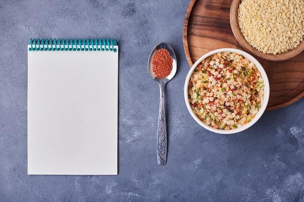 Een kopje bonensalade met een receptenboek opzij.