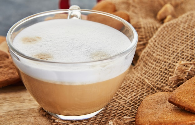 Een kopje cappuccino en peperkoekkoekjes in de vorm van een hart op een jute
