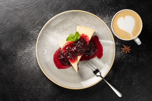 Een kopje cappuccino en twee plakjes cheesecake op een rond bord besprenkeld met aardbeienjam en gegarneerd met poedersuiker en muntblaadjes