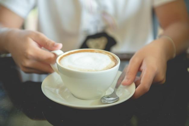 Een kopje cappuccino in de hand van een vrouw