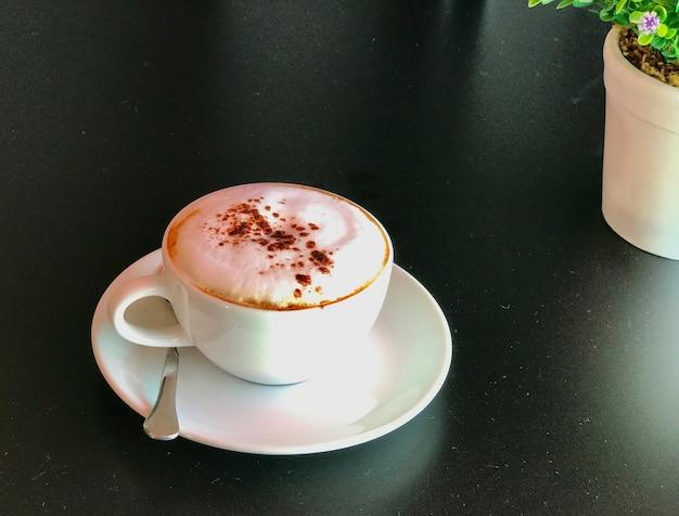 Een kopje cappuccino koffie op zwarte tafel