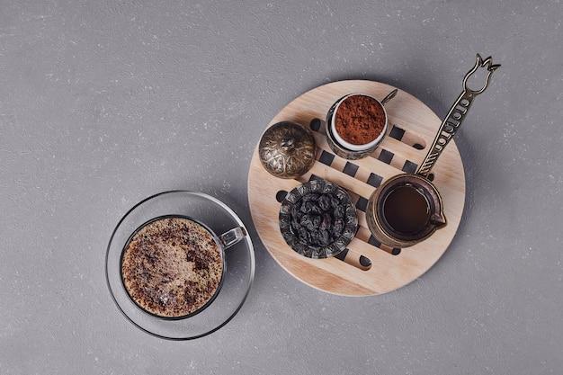 Een kopje cappuccino met kaneelpoeder eromheen.