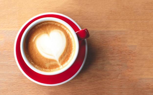 Een kopje cappuccino met latte art op een houten achtergrond.
