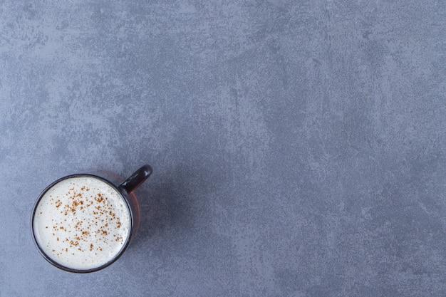 Een kopje cappuccino met melk, op de blauwe tafel.