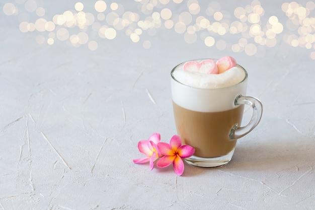 Een kopje cappuccino met twee marshmallow-hartjes erop met bokeh.