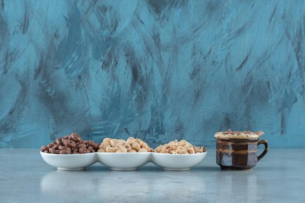 Een kopje cappuccino naast cornflakes in kommen, op de blauwe tafel.