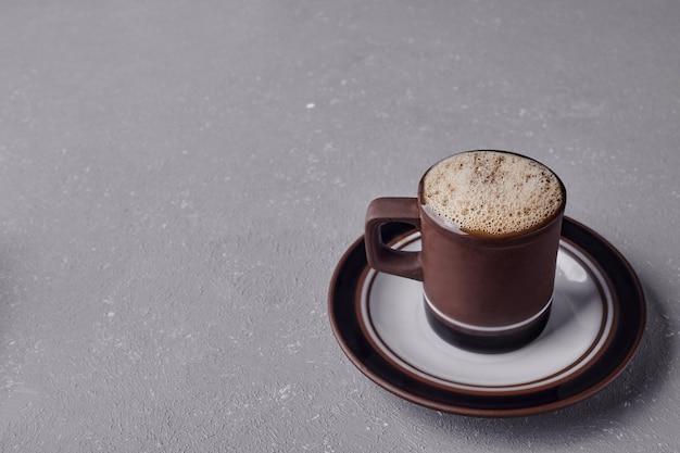 Een kopje cappuccino op een grijze achtergrond.