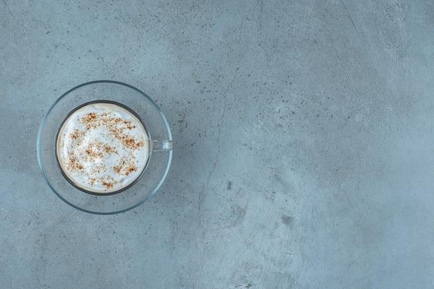 Een kopje cappuccino op een schotel, op de blauwe achtergrond.