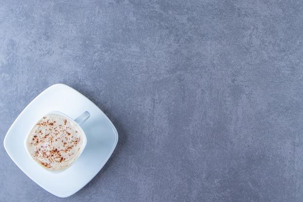 Een kopje cappuccino op een schoteltje, op de blauwe tafel.