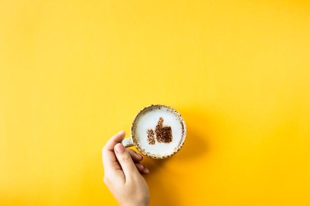 Een kopje cappuccino waarop een glimlach als een duim omhoog wordt getekend
