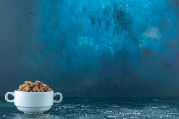 Een kopje chocolade maïs ringen, op de blauwe achtergrond. hoge kwaliteit foto