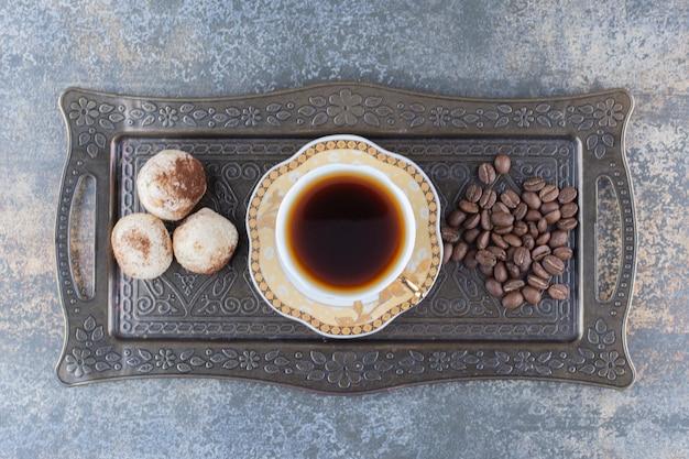 Een kopje donkere koffie met koekje op donker bord. hoge kwaliteit foto