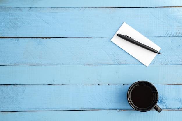 Een kopje drank en een papieren notitieblok met een zwarte pen op een blauw hout