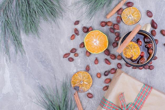 Een kopje drank met droge stukjes sinaasappel, heupen en kaneel.