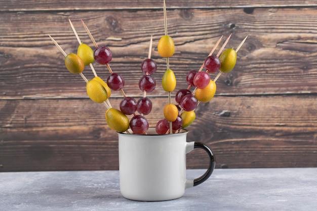 Een kopje eetstokjes met rijpe rode druiven en kumquats op een marmer.