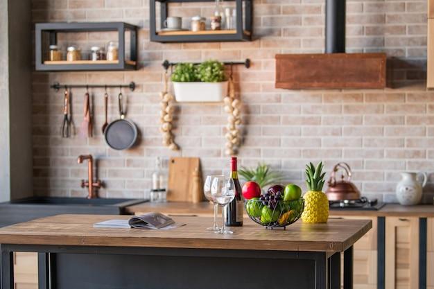 Een kopje en gebak op een bord, wijnglazen, een fles wijn en fruit staan op de tafel in het keukeninterieur