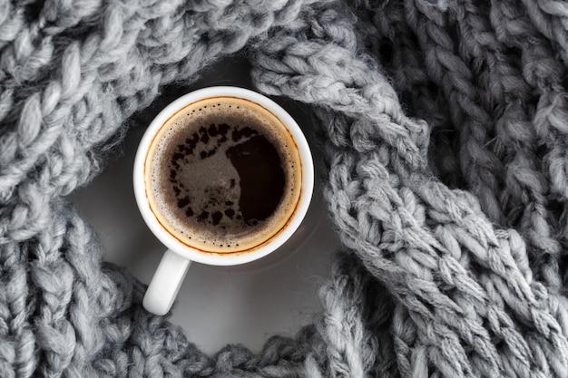 Een kopje espresso, gehuld in een wollen, warmgrijze sjaal. bovenaanzicht