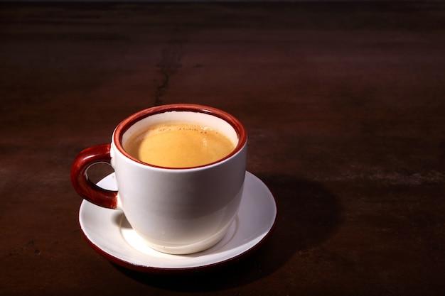Een kopje espresso op een donkere houten achtergrond