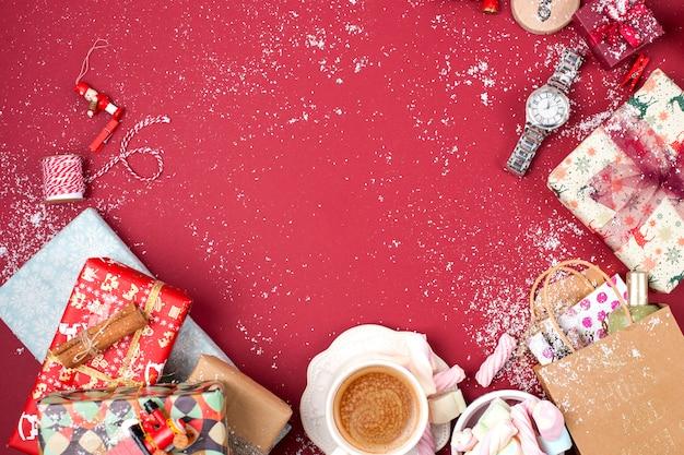 Een kopje geurende koffie en kerstversiering op een rode achtergrond. geschenken en syootrizy voor kerstmis. bovenaanzicht frame. kopieer ruimte