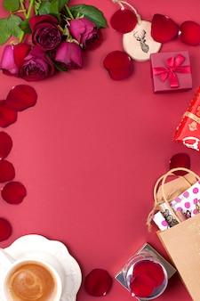 Een kopje geurende koffie en kerstversiering op een rode achtergrond. rozen, geschenken en kerstverrassingen. bovenaanzicht frame. kopie spase
