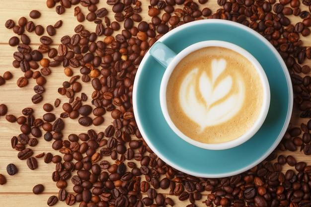 Een kopje geurige koffie in schuim op een houten tafel. latte kunst. koffiebonen.