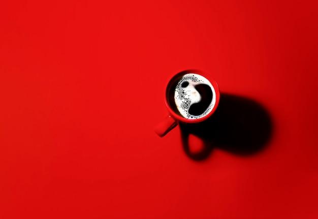 Een kopje geurige koffie op een rode achtergrond voor uw ontwerp. schaduw van de beker. reclame voor koffie.