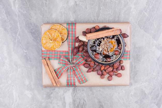 Een kopje glintwine op een geschenkdoos met kruiden en specerijen